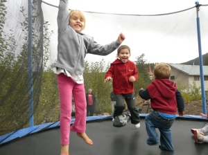 Kateri and Isaiah jumping with their neighbour friend, Carter